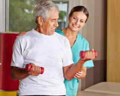 elderly man doing exercise assisted by caregiver