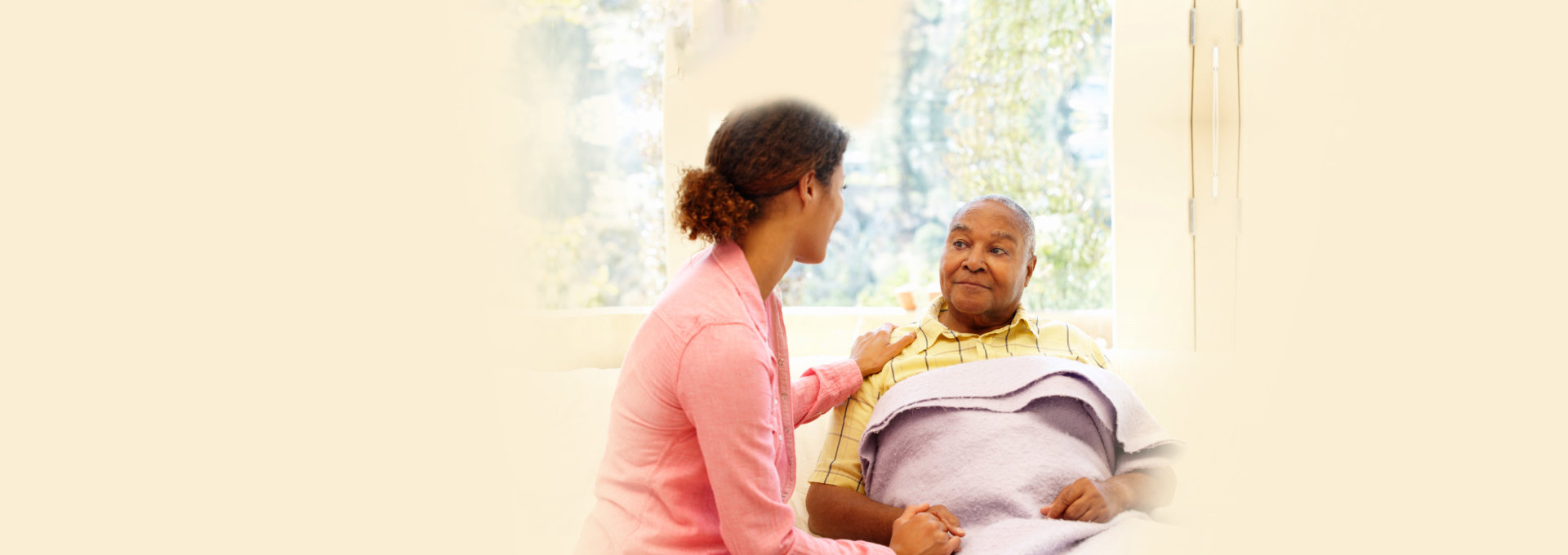 caregiver and elderly man talking in bed