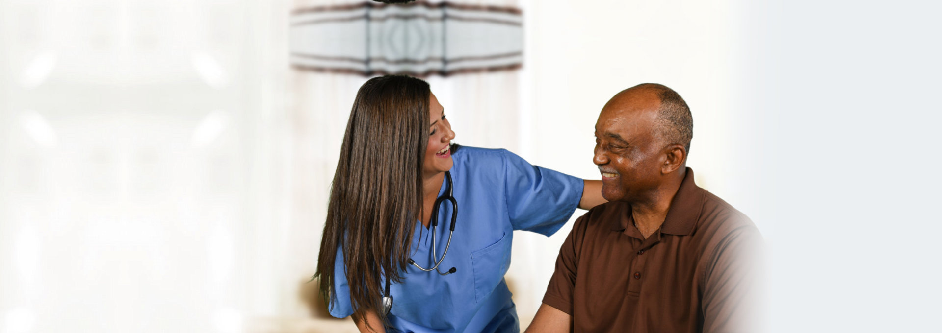 caregiver and elderly man smiling with each other