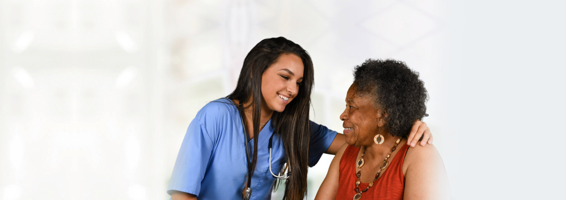caregiver and elderly woman smiling with each other