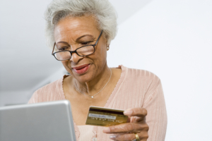 elderly woman using laptop while holding a card