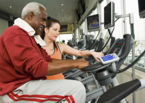 caregiver assisting elderly man using exercise bike