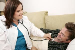 caregiver monitoring elderly man's heartbeat
