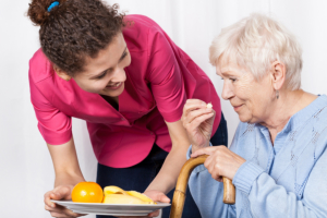 caregiver serving meal to elderly woman