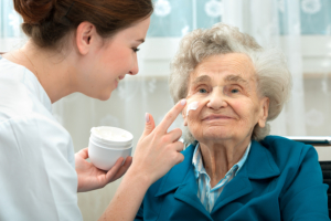caregiver applying facial cream on elderly woman's face