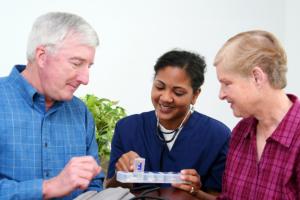 caregiver discussing about elderly man's medicine